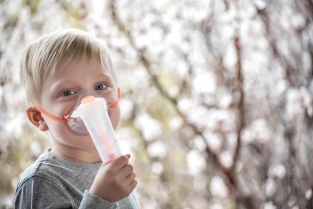 Garçon blond en inhalateur masque respiratoire d'arbres en fleurs. traitement à domicile. la prévention