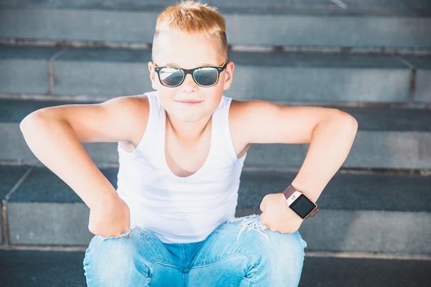 Garçon blond en jeans et t-shirt blanc est assis sur les marches
