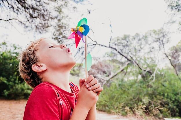 Garçon blond jouant dans une forêt avec un moulinet coloré soufflant de l'air avec une grimace.