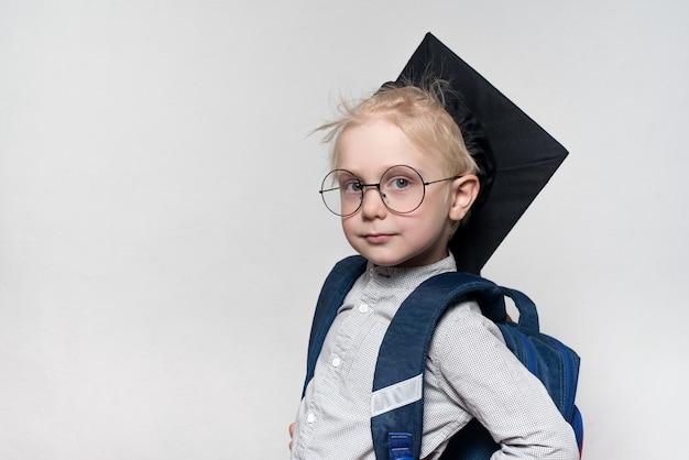 Garçon blond à lunettes, un chapeau académique et un cartable