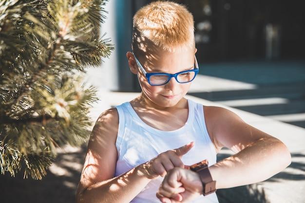 Garçon blond à lunettes regarde sa montre dans le parc.