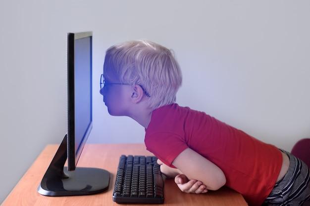 Garçon blond avec des lunettes se trouve son nez enfoui dans un moniteur. internet et préscolaire