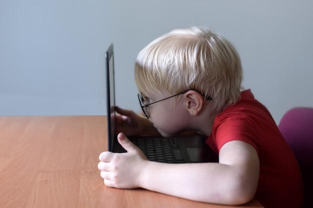 Garçon blond avec des lunettes se trouve son nez enfoui dans un ordinateur portable. internet et préscolaire