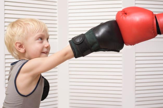 Garçon blond avec la main dans un gant rouge. émotions