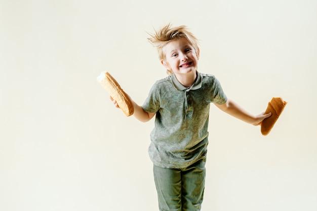 Un garçon blond mange une baguette parfumée, des pâtisseries fraîches. savoureux petit déjeuner