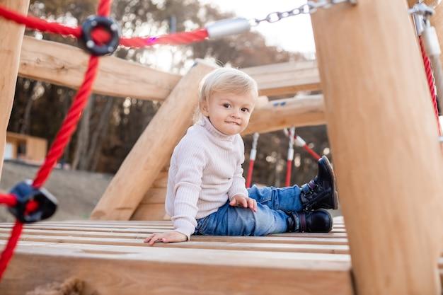 Garçon blond mignon jouant sur une aire de jeux en bois à l'extérieur