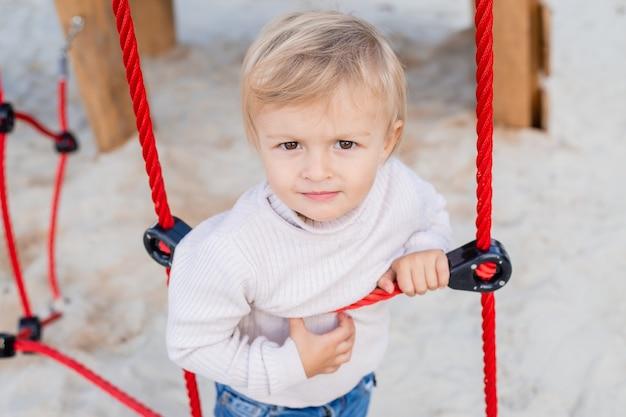 Garçon blond mignon jouant sur une échelle de corde à l'extérieur