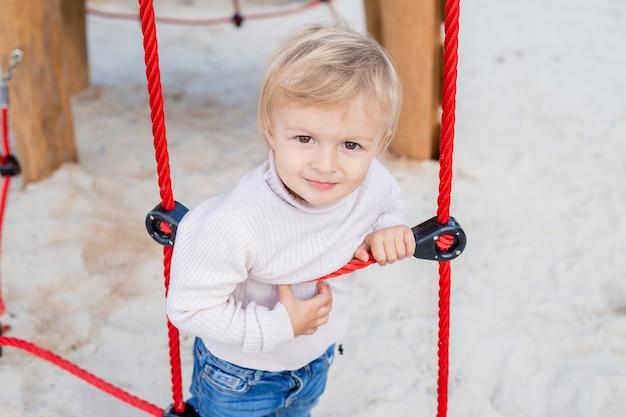 Garçon blond mignon monte une échelle de corde dans l'air frais