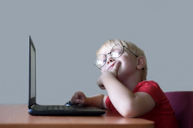 Garçon blond pensif avec des lunettes se trouve à un ordinateur portable. internet et préscolaire
