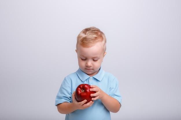 Garçon blond avec une pomme dans ses mains