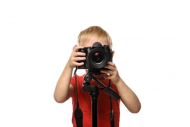 Un garçon blond prend des photos avec un appareil photo reflex. vue de face