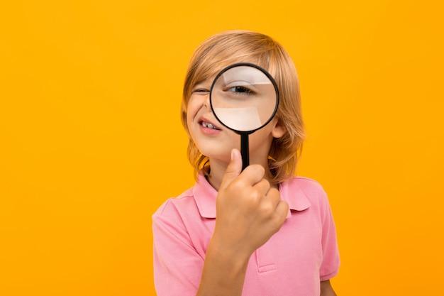 Garçon blond regarde à travers une loupe grossissante sur jaune