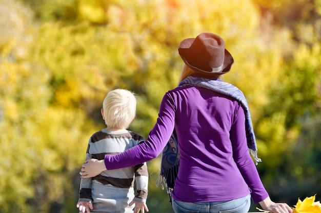 Garçon blond avec sa mère assise sur la rive du fleuve