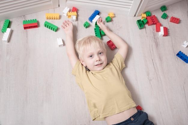 Un garçon blond se trouve sur le sol entre des blocs de construction