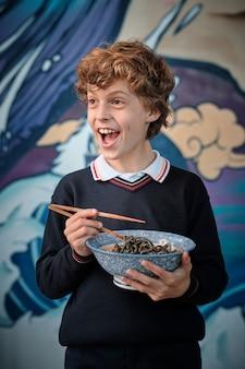 Garçon blond souriant aux cheveux bouclés ramassant un bol de ramen avec des baguettes à la main.