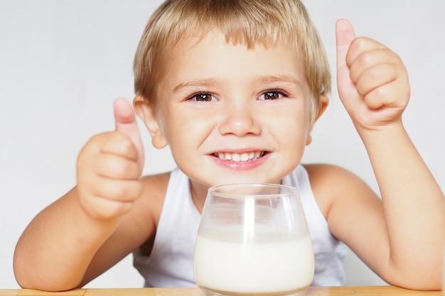 Un garçon blond souriant aux yeux bruns boit du lait dans un verre sur une table en bois et montre sa classe avec ses mains.
