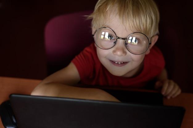 Garçon blond souriant avec des lunettes sur un ordinateur portable