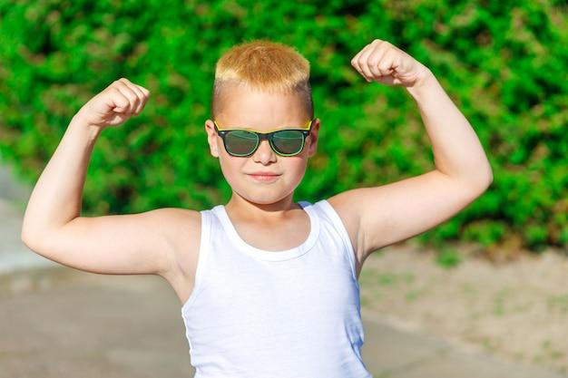 Garçon blond en t-shirt blanc montre les muscles