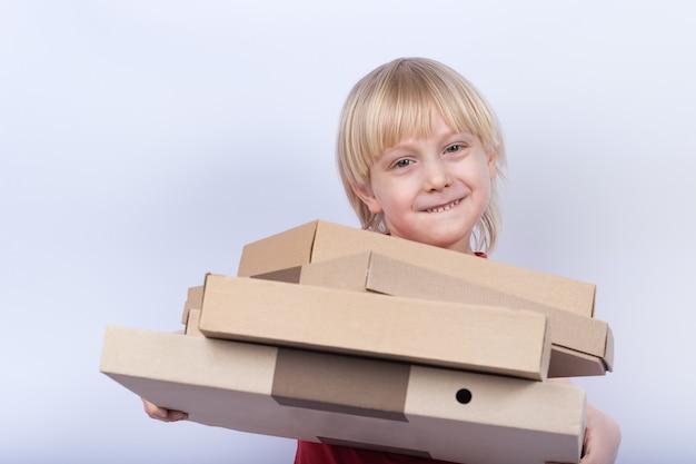 Garçon blond tenant de nombreuses boîtes à pizza sur fond blanc. livraison de pizza à domicile concept.