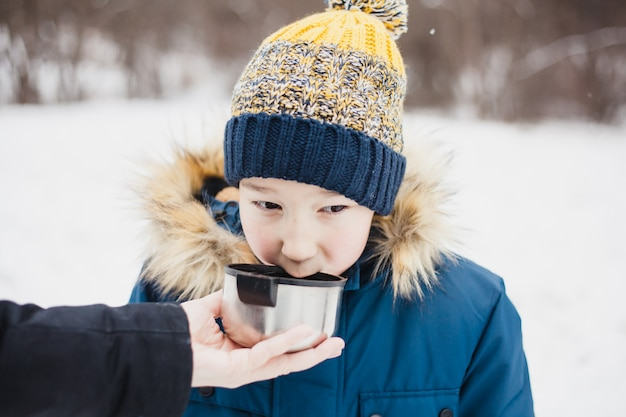 Un garçon boit dans un thermos de thé ou une boisson, marche d'hiver, randonnée pédestre, hiver, vêtements d'hiver