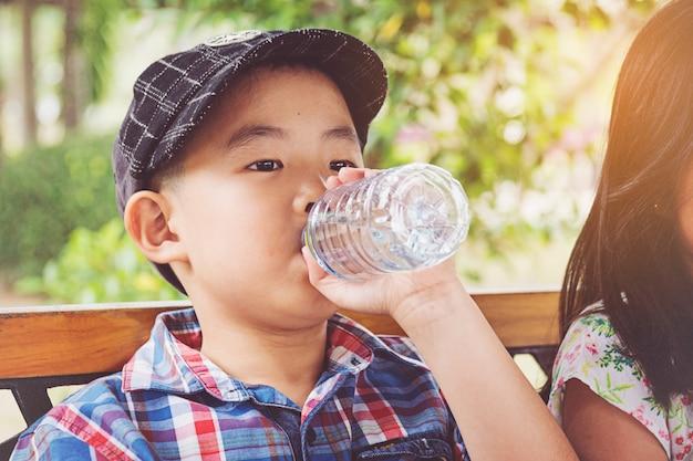 Un garçon boit de l'eau d'une bouteille