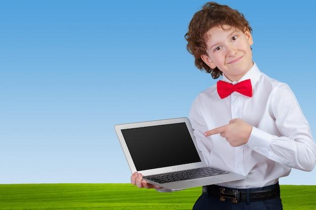 Garçon bouclé en costume formel avec ordinateur portable