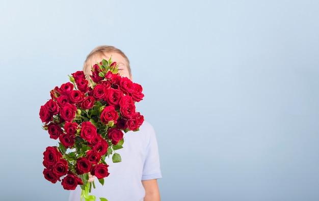 Garçon avec un bouquet de roses rouges comme cadeau pour la fête des mères ou la saint-valentin