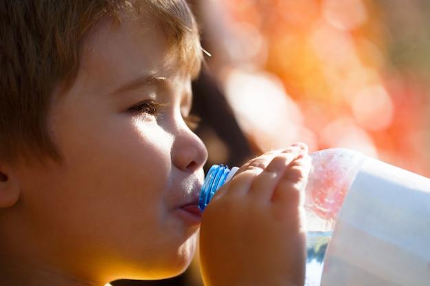Garçon bouteille d'eau. jeune garçon tenant une bouteille d'eau fraîche.