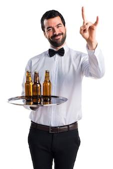 Garçon avec des bouteilles de bière sur le plateau faisant un geste de corne