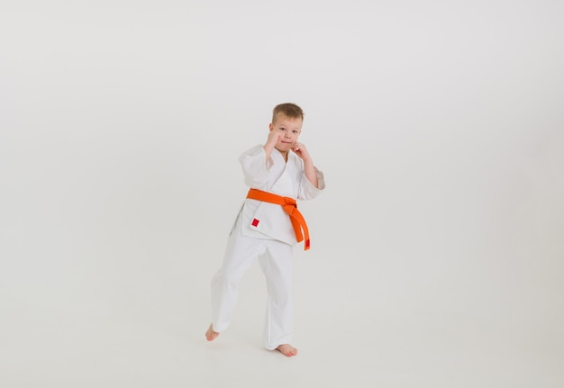 Un garçon boxer dans un kimono blanc avec une ceinture orange sur fond blanc