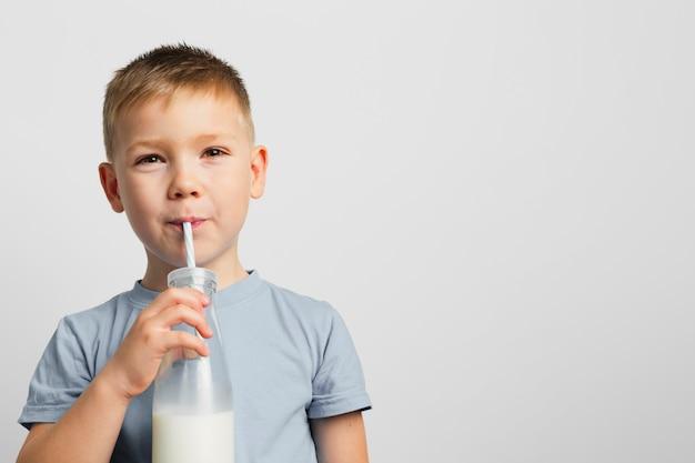 Garçon buvant du lait avec de la paille