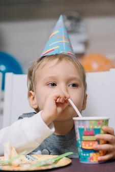Garçon buvant à la fête d'anniversaire