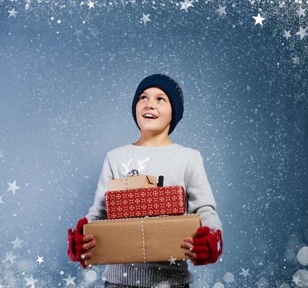 Garçon avec cadeau de noël parmi la neige qui tombe