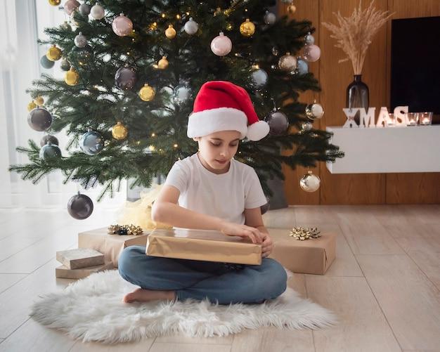 Garçon avec des cadeaux joue près de l'arbre de noël. intérieur du salon avec sapin de noël et décorations. nouvelle année. donner en cadeau.