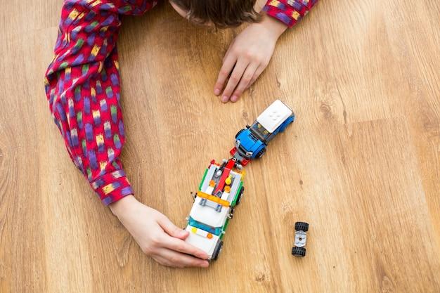 Garçon avec camion remorqueur jouet. enfant jouant avec un camion jouet. déménagement à la station-service automobile. l'aide est arrivée juste à temps.