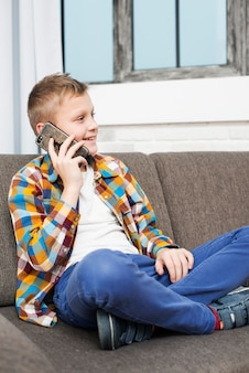 Garçon sur le canapé faisant un appel téléphonique