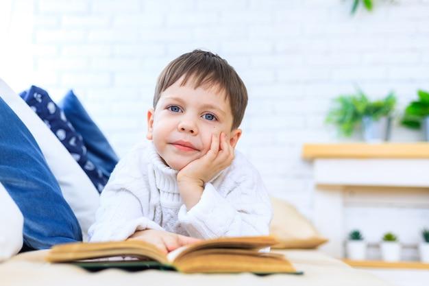 Le garçon sur le canapé lit un livre. lire un livre. chambre lumineuse. le garçon est allongé sur le canapé. article sur les loisirs des enfants. le développement des enfants. les livres pour enfants.