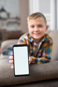 Garçon sur un canapé montrant l'écran du smartphone