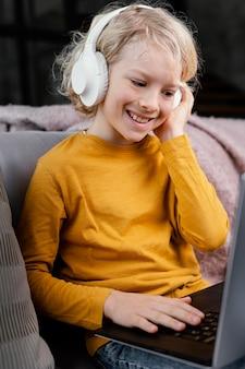Garçon sur canapé avec ordinateur portable et écouteurs