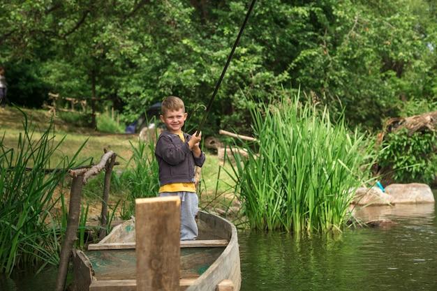 Garçon avec canne à pêche pêche dans un bateau en bois
