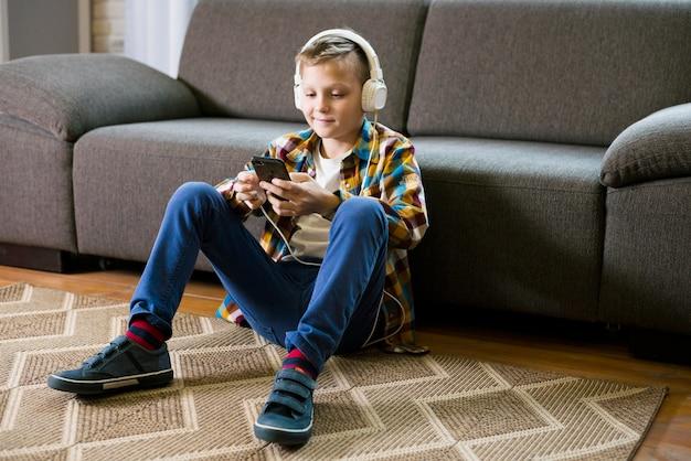 Garçon avec un casque à l'aide de smartphone