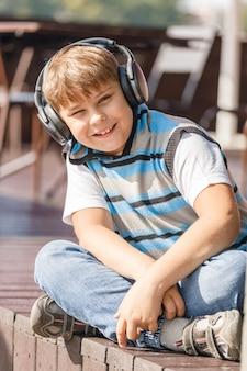 Garçon avec un casque d'écoute de la musique assis sur la véranda à la maison