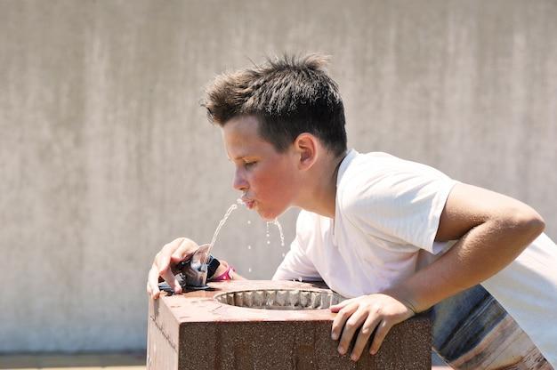 Garçon caucasien de 11 ans boit de l'eau