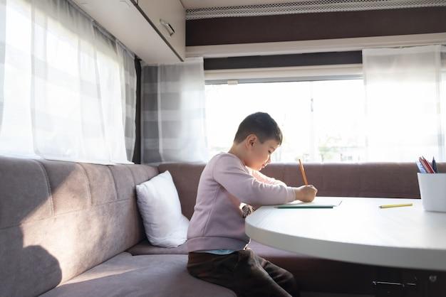 Un garçon caucasien d'un an peint à l'intérieur d'une caravane lors d'un week-end