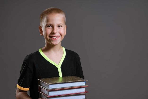 Un garçon caucasien gai dans un t-shirt noir tient une pile de livres sur fond gris. notion d'éducation