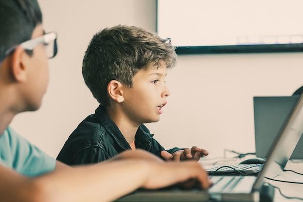 Garçon caucasien, lecture de la tâche à haute voix pendant la leçon