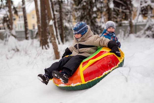 Garçon caucasien portant des vêtements d'hiver glissant sur un tube un autre garçon assis sur un toboggan