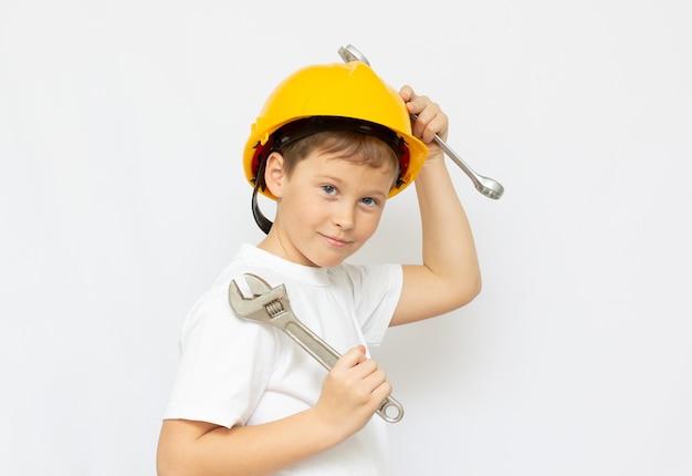 Le garçon à la chemise blanche et casque de construction jaune, tenant une clé à pipe dans les mains sur fond blanc