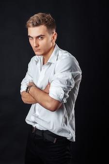 Le garçon en chemise blanche sur fond noir. le concept de l