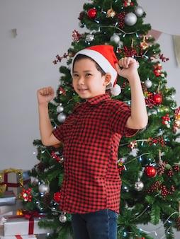 Un garçon en chemise rouge est heureux et amusant de fêter noël avec un sapin de noël